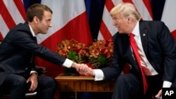 FILE - President Donald Trump shakes hands with French President Emmanuel Macron during a meeting at the Palace Hotel, Sept. 18, 2017, in New York.