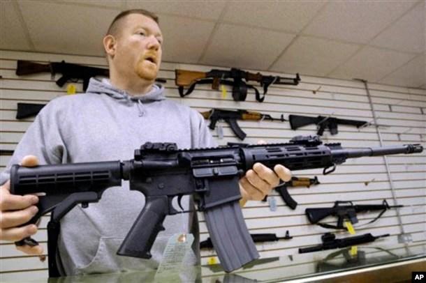 Ông John Jackson, đồng sở hữu cửa hàng vũ khí Capitol City ở Springfield, Illinois, đưa ra một khẩu súng trường tấn công AR-15 để bán cho khách hàng.