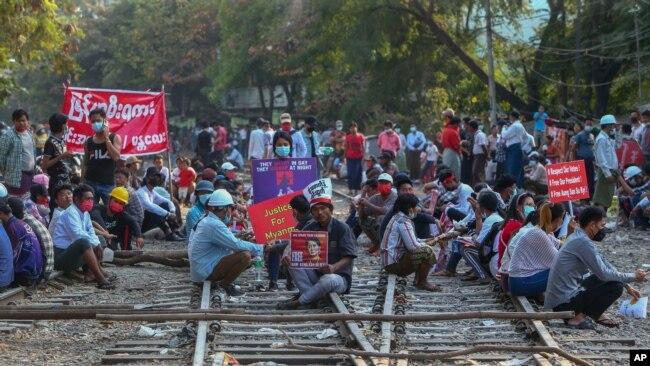 示威者在曼德勒举行反对政变的抗议,有的人坐在铁轨上。(2021年2月18日)