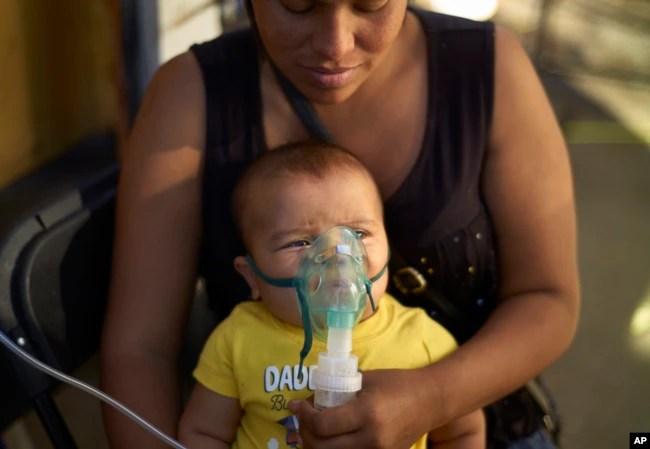 La migrante hondureña Janet Zuniga sostiene a su hijo Linder de cinco meses de edad, mientras recibe tratamiento médico fuera de un refugio, el lunes 26 de noviembre de 2018, en Tijuana, México.