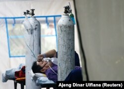Seorang pasien COVID-19 bernapas dengan masker non-rebreather di tenda darurat sebuah rumah sakit di Jakarta, 24 Juni 2021. (Foto: REUTERS/Ajeng Dinar Ulfiana)
