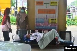 Seorang pasien terbaring di bangku saat mengantre untuk dirawat di ruang gawat darurat RSUP Dr. Loekmono Hadi, di tengah pandemi virus corona (COVID-19) di Kudus, Provinsi Jawa Tengah, Indonesia, 2 Juni 2021. (REUTERS)