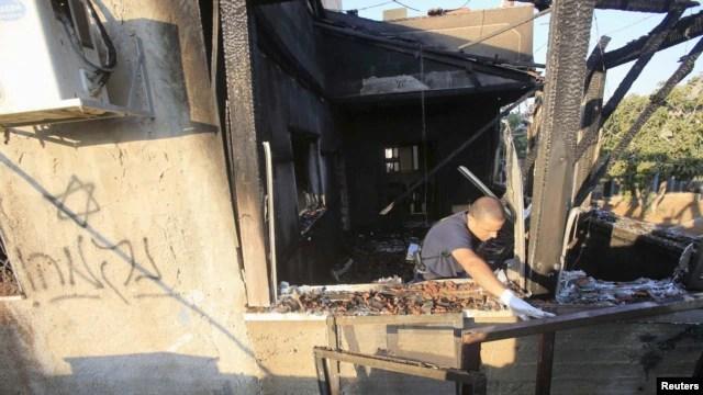 Một viên cảnh sát Israeli xem ngôi nhà bị hư hại nặng nề trong vụ phóng hỏa ở làng Duma gần thành phố Nablus ở Bờ Tây, ngày 31 tháng 7, 2015.
