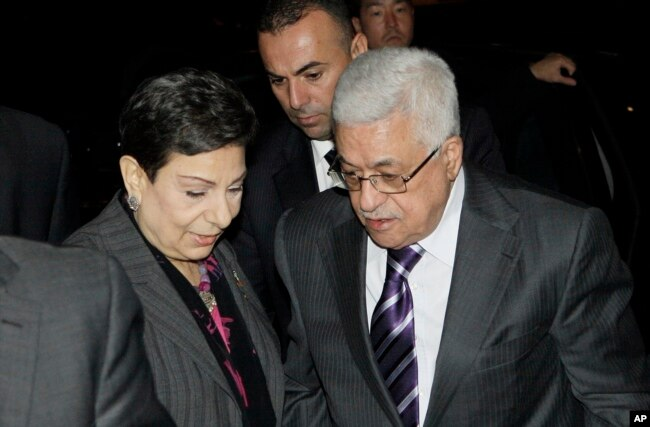 Palestinian President Mahmoud Abbas, right, is greeted by Hanan Ashrawi, left, legislator and activist, as he arrives at his hotel in New York, Monday, Sept. 19, 2011, to attend the 66th General Assembly session of United Nations.
