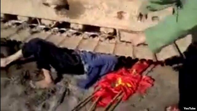 Nạn nhân nằm dưới bánh của máy xúc trong đoạn video clip gây xôn xao dư luận.