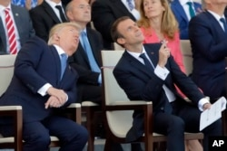 FILE - French President Emmanuel Macron, right, and U.S. President Donald Trump watch the traditional Bastille Day military parade, including military jet flyovers, on the Champs Elysees, in Paris, July 14, 2017.