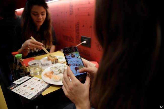 Chiara Valenzano, right, photographs her food as she has lunch with her friend Giulia Terranova at the 'This is not a Sushi bar' restaurant, in Milan, Italy, Oct. 16, 2018. At the restaurant, payment can be made according to the number of Instagram followers one has.