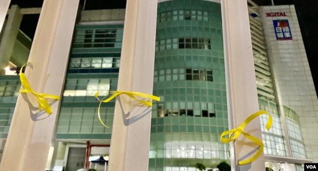 有市民在苹果日报大楼外的铁栏上绑上象征自由的黄丝带。 (美国之音/汤惠芸)