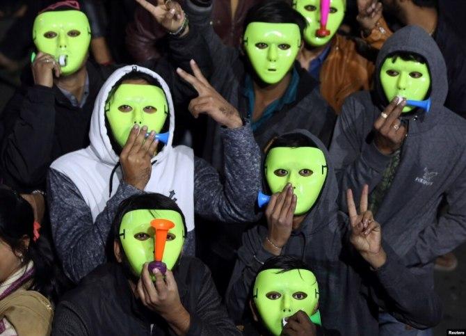 Người dân đeo mặt nạ, thổi kèn trong lúc tham dự một sự kiện đếm ngược chào đón năm mới tại thành phố Ahmendabad, Ấn Độ, 31/12/2018.