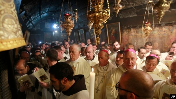 Latin clergies gather in the Grotto at the end of the midnight mass in Saint Catherine's Church where Christians believe the Virgin Mary gave birth to Jesus Christ, in the adjacent Church of the Nativity in Bethlehem, Dec. 25, 2016.