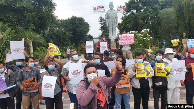 Jurnalis Surabaya melakukan aksi menolak kekerasan yang dilakukan polisi terhadap jurnalis Tempo di Surabaya, Nurhadi, saat lakukan peliputan (Foto:VOA/Petrus Riski).