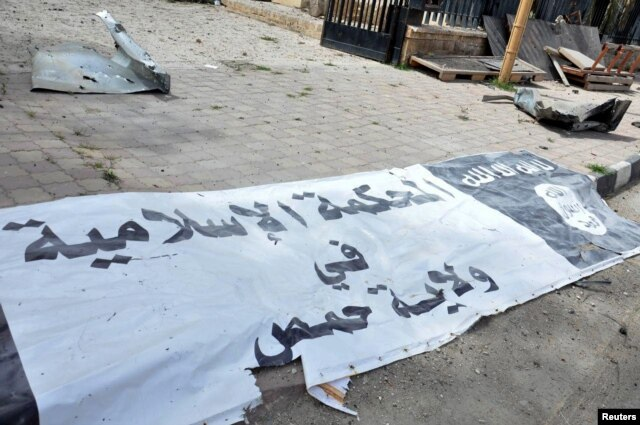 FILE - A banner belonging to the Islamic court of the Islamic State is seen on the ground after forces loyal to Syria's President Bashar al-Assad recaptured Palmyra city in this handout picture provided by SANA on March 27, 2016.