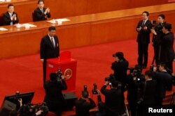 Chinese President Xi Jinping pauses after casting his ballot during a vote on a constitutional amendment lifting presidential term limits, at the third plenary session of the National People's Congress (NPC) at the Great Hall of the People in Beijing.