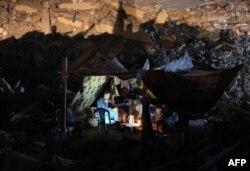 Warga Palestina duduk di tenda yang telah didirikan di atas reruntuhan bangunan yang hancur akibat serangan udara Israel baru-baru ini, di Kota Gaza, pada 24 Mei 2021. (Foto: AFP)
