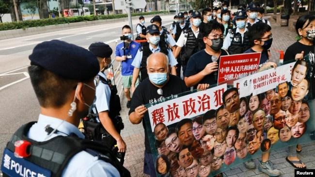 香港支持民主的四名抗议者在中国国庆这一天不惧警察的监视,手举标语牌要求释放政治犯。(2021年10月1日)