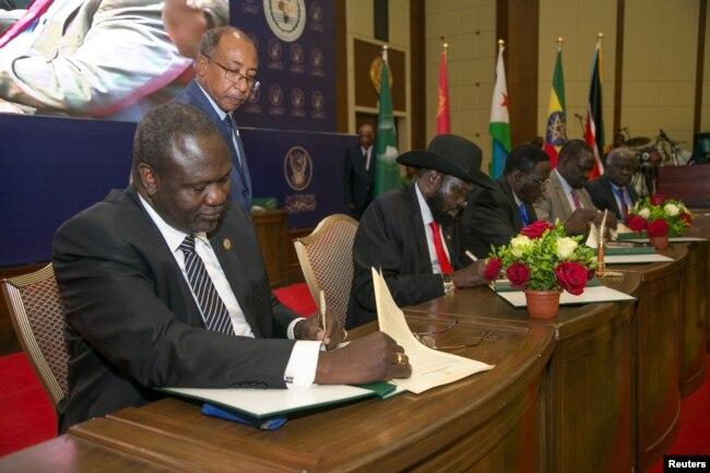 South Sudanese rebel leader Riek Machar (L), and South Sudan's President Salva Kiir sign a ceasefire and power sharing agreement in Khartoum, Sudan, Aug. 5, 2018.