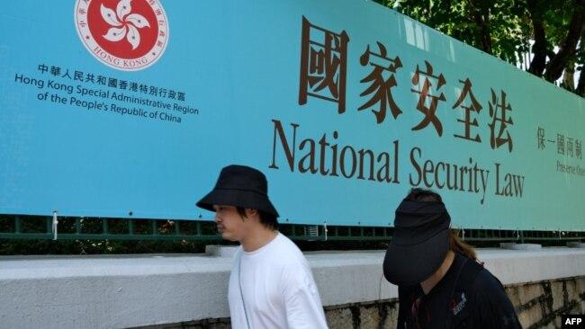 行人走过香港街头港版国安法的宣传牌。(2020年7月15日)