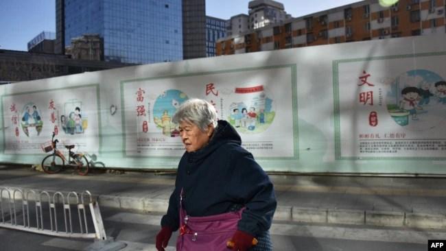 """一名中国妇女走过北京一处建筑工地,背后的宣传牌上写着""""文明""""""""民主""""""""富强""""""""友善""""""""诚信""""。(法新社 2018年12月4日)"""