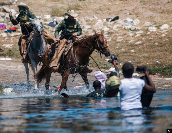 资料照片:美国边境巡逻人员骑马阻止海地移民从格兰德河的墨西哥一侧淌水进入美国边境城市德尔里奥。(2021年9月19日)