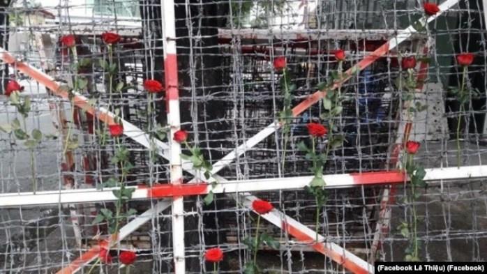 """Người dân cài hoa hồng lên hàng rào kẽm gai trước đó được dùng để quây khu vực """"trại giam"""" của công an ở Công viên Tao Đàn, quận 1 TP HCM. (Facebook Lê Thiệu)"""