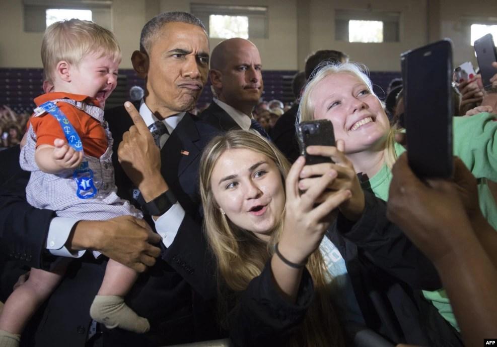 在俄亥俄州哥伦布市,美国总统奥巴马在克林顿竞选大会上发表讲话后,抱着婴儿,和支持者在一起(2016年11月1日)。奥巴马大力为克林顿造势,强烈批评川普