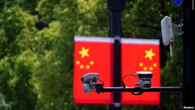 上海一家商场悬挂的中国国旗和国旗前的监控摄像头。(2021年5月5日)