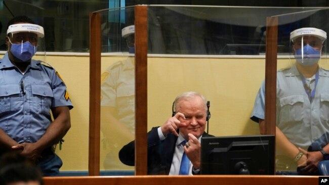 波黑塞族前军队总司令姆拉迪奇在荷兰海牙的国际法庭上模仿拍照动作。(2021年6月8日)