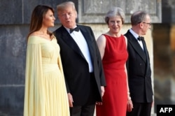 U.S. first lady Melania Trump, U.S. President Donald Trump, Britain's Prime Minister Theresa May, and her husband, Philip May, stand on the steps in the Great Court to watch the bands of the Scots, Irish and Welsh Guards perform a ceremonial welcome.