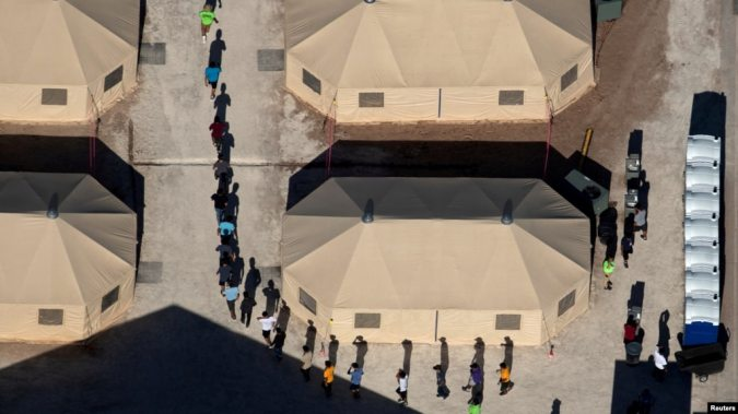 FILE - Immigrant children are led by staff in single file between tents at a detention facility next to the Mexican border in Tornillo, Texas, June 18, 2018.