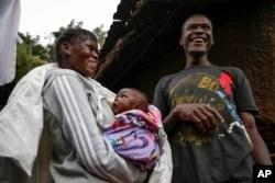 Veronica Atieno, kiri, menggendong putrinya Shaniz Joy Juma, tengah, yang dilahirkan sebulan sebelumnya oleh dukun bayi tradisional selama jam malam menjelang senja, ditemani suaminya Gabriel Owour Juma, kanan, di daerah kumuh Kibera di Nairobi. (Foto: AP)