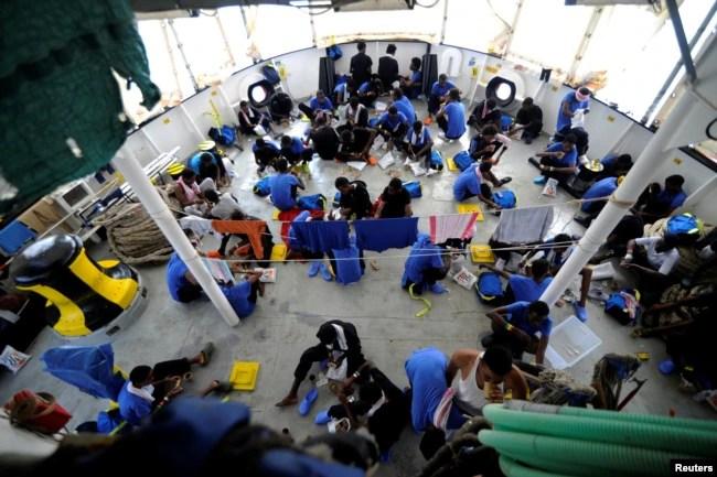 FILE - Migrants are seen on board the MV Aquarius, in the Mediterranean Sea, between Malta and Linosa, Aug. 14, 2018.