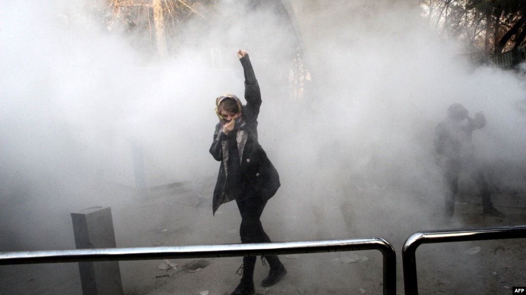 FILE - An Iranian woman raises her fist amid the smoke of tear gas at the University of Tehran during a protest, in Tehran, Iran, Dec. 30, 2017.