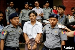 Detained Reuters journalist Kyaw Soe Oo and Wa Lone are escorted by police as they leave after a court hearing in Yangon, Myanmar, August 20, 2018.