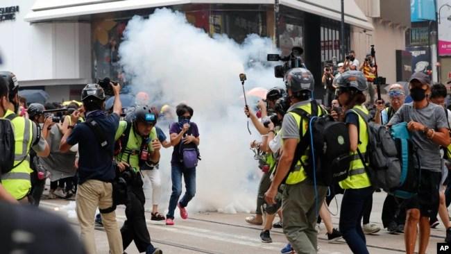 Un grupo de manifestantes corre después que la policía les lanzó gas lacrimógeno en el distrito comercial deHong Kong, cuando se negaron a dispersarse. Domingo 29 de septiembre de 2019.