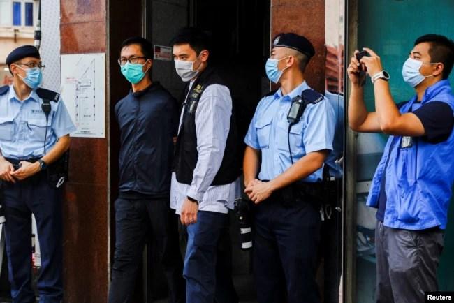 香港警察逮捕了支联会成员之一梁锦伟(左二)。(2021年9月9日)