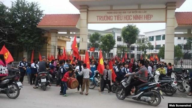 Hàng trăm học sinh tiểu học, trung học cơ sở tập trung trước cổng trường Ninh Hiệp phản đối việc xây trung tâm thương mại. (ảnh chụp từ trang thanhnien).