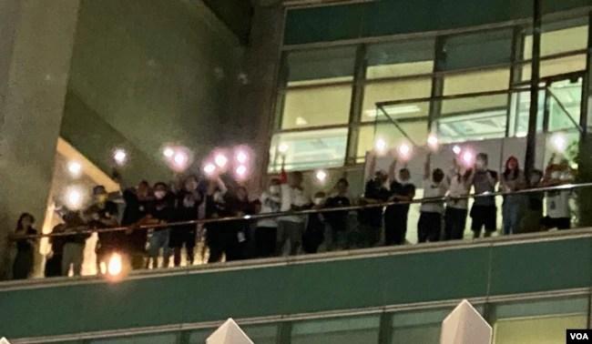 一批苹果日报编采人员6月24日凌晨在苹果日报大楼平台高举手机灯,向大楼外声援的市民表达谢意 (美国之音/汤惠芸)