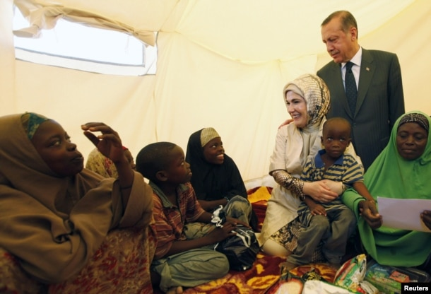 FILE - Turkey's Prime Minister Recep Tayyip Erdogan (top) and his wife Emine Erdogan visit a camp for displaced people in Mogadishu, Aug. 19, 2011.