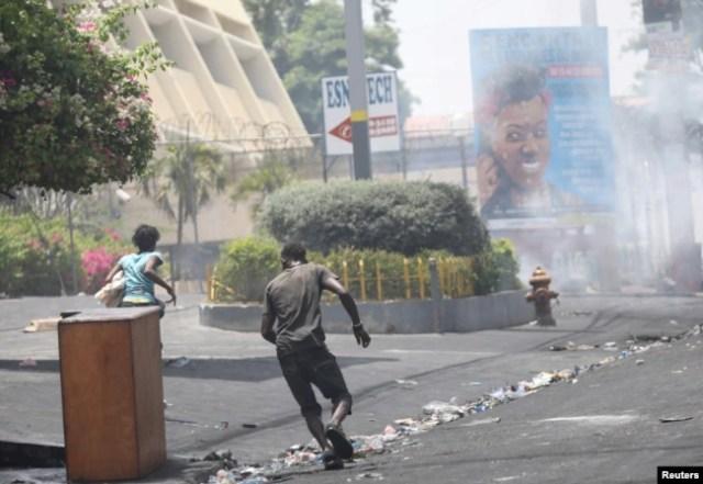 Gente huye mientras la policía usa gas lacrimógeno para dispersar disturbios en una calle de Puerto Príncipe, Haití, el 8 de julio de 2018. REUTERS / Andres Martinez Casares -