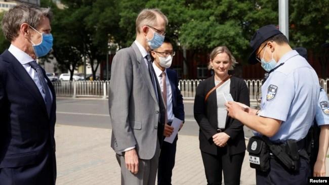 一名中国警察在北京市第二人民法院外查看澳大利亚驻华大使傅关汉 (Graham Fletcher)的身份证件。(2021年5月27日)