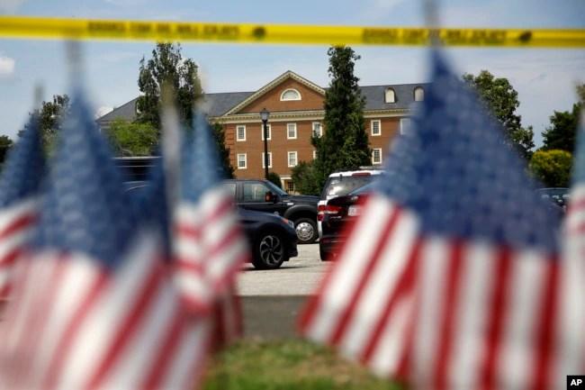 Banderas estadounidenses forman parte de un altar improvisado al borde de un cordón policial frente a un edificio municipal que fue el escenario de un tiroteo, el sábado 1 de junio de 2019, en Virginia Beach, Virginia.