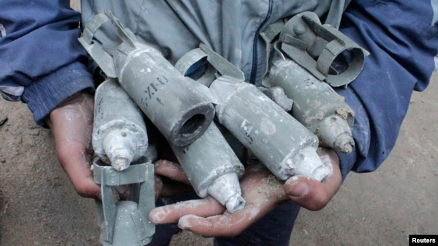 A boy holds unexploded cluster bombs after jet shelling by forces loyal to Syria's President Bashar al-Assad in the al-Meyasar district of Aleppo, Feb. 21, 2013.