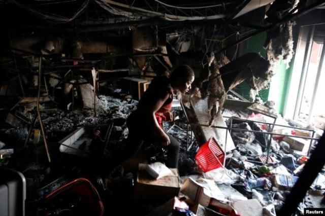 Una mujer entra a un supermercado que fue saqueado durante las protestas contra los aumentos de los precios del combustible en Puerto Príncipe, Haití, el 8 de julio de 2018. REUTERS / Andres Martinez Casares
