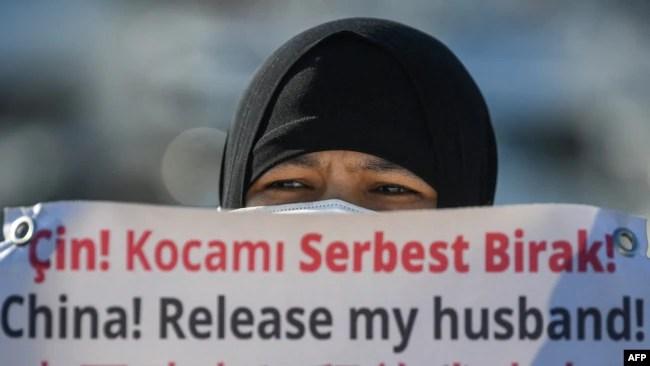 资料照片:一名维吾尔妇女在中国驻伊斯坦布尔领事馆附近举牌抗议,要求中国政府释放其丈夫。(2021年2月22日)