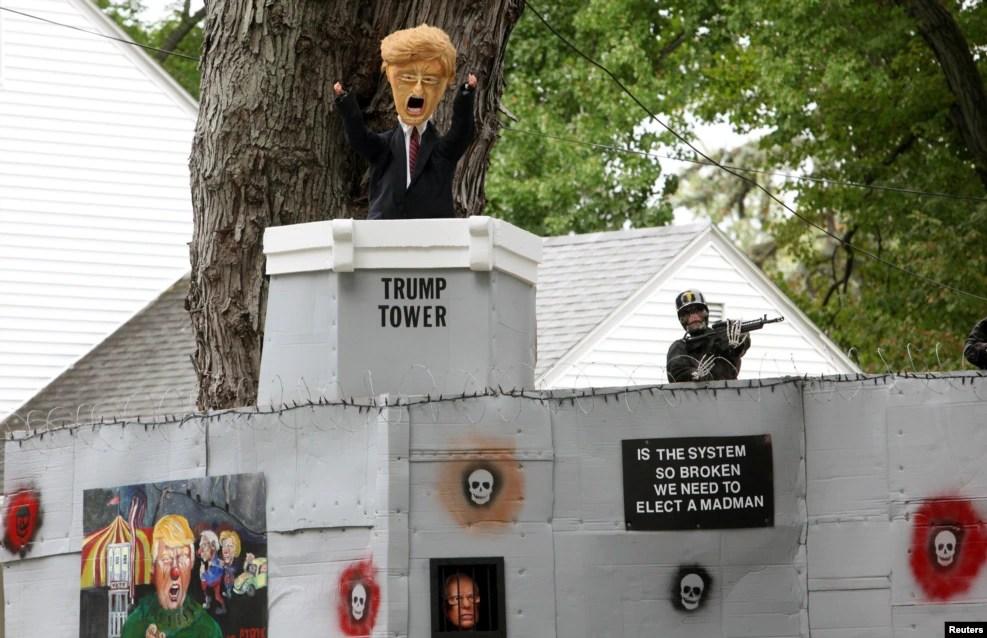 """康涅狄格州一家民宅上的万圣节装饰,有三名参选人和川普大楼的漫画形象。还有文字说""""体制已经坏到如此地步以至于我们需要选出一个男疯子吗?"""""""