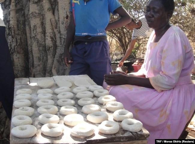 A woman sells doughnuts at an open-air bakery in Arubela, Uganda, Feb. 14, 2018.