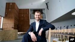Pastor Jan Korditschke SJ, yang akan memimpin pemberkatan untuk pasangan sesama jenis di Berlin pada minggu mendatang, berpose untuk foto di Gereja Kanisius di Berlin, Jerman, Jumat, 7 Mei 2021. (AP/Michael Sohn)