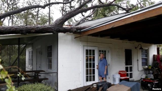 Andrew Lamonica inspecciona un árbol que cayó en su casa después del paso del Huracán Michael en Panama City Beach, Florida. Octubre 10, 2018