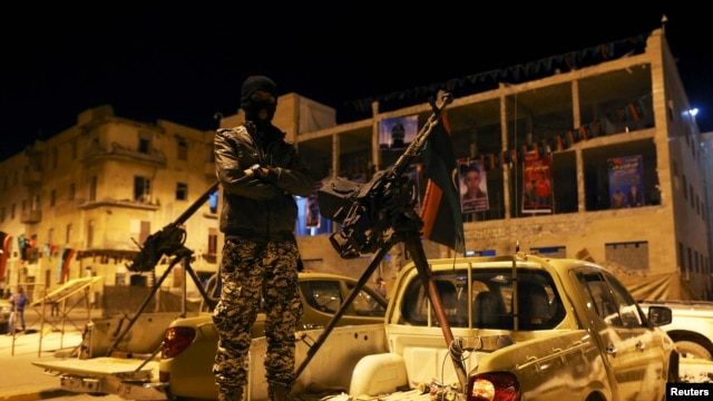 FILE - A member of a heavily armed militia group is seen in Benghazi.