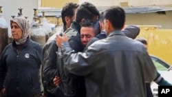 Men grieve outside a hospital following Turkish airstrikes on the Syrian Kurdish enclave of Afrin, northwestern Syria, Feb. 14, 2018. Nearly a month into Turkey's offensive in Afrin, hundreds of thousands of Syrians are hiding from bombs and airstrikes, trapped while Turkish troops and their allies are bogged down in fierce ground battles against formidable opponents.